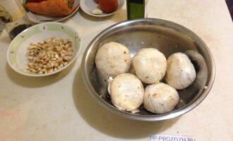 Шаг 3: Шляпки грибов замаринуйте в смеси из 2 ложек оливкового масла, одного зубчика чеснока, измельченного через пресс, и щепотки соли.