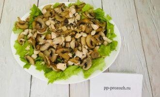 Шаг 10: Сверху салата выложите обжаренные грибы и куриную грудку.