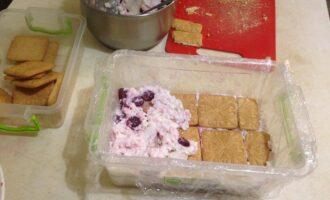 Шаг 5: Глубокую форму застелите пищевой пленкой так, чтобы свисали края. Выкладывайте в нее слоями печенье и крем, пока продукты не закончатся.