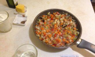 Шаг 4: На антипригарную сковороду  налейте 2 столовые ложки оливкового масла, поставьте на плиту. Выложите порезанный лук, овощи, добавьте полстакана воды и тушите 15-20 минут.
