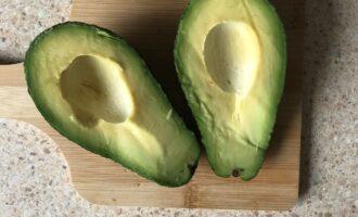 Шаг 2: Разрежьте авокадо пополам и выньте из него косточку.