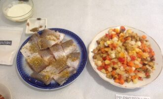 Шаг 2: Рыбу посолите, посыпьте приправой для рыбы и оставьте мариноваться. Замороженные овощи высыпьте в тарелку, чтобы немного разморозились.