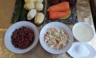 Шаг 1: Подготовьте ингредиенты винегрета: свеклу, картофель, морковь, огурцы, фасоль, квашеную капусту, растительное масло и соль.