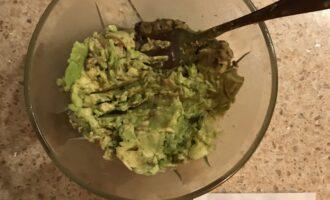 Шаг 8: Половину авокадо разомните вилкой. Это будет первый слой.
