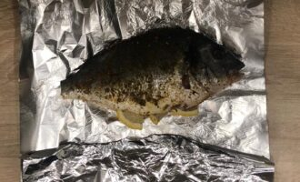 Шаг 4: Внутрь рыбы вложите дольки лимона, заверните в фольгу и поставьте в разогретую до 180 градусов духовку на 20 минут.