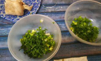 Шаг 3: Зелень нарежьте и разложите по формам. Вытащите курицу, чтобы остыла. А в бульон всыпьте желатин, и тщательно размешайте.