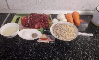 Шаг 1: Подготовьте все компоненты блюда: мясо, рис бурый, лук, морковь, масло, соль, чеснок и перец. Хорошо промойте бурый рис, залейте кипятком и оставьте на 3 часа. На фото промытый и замоченный рис