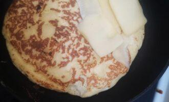 Шаг 4: Как перевернете блин, сверху выложите ломтики сыра.
