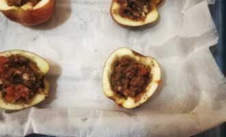 Шаг 6: Разогрейте духовку до 150 градусов, застелите пергаментом противень. В яблоки положите начинку, сверху посыпьте корицу. Отправьте в духовку на 15 минут.
