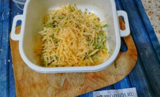 Шаг 2: Натрите кабачок на крупной терке. Уберите лишнюю жидкость. Натрите сыр и добавьте к кабачку.
