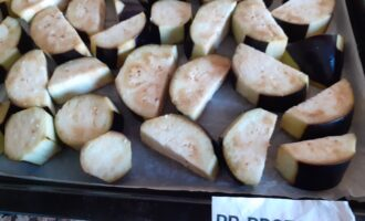 Шаг 3: Застелите противень кулинарной бумагой и уложите баклажаны. Поставьте противень в заранее разогретую до максимума духовку и тушите 10-15 минут.