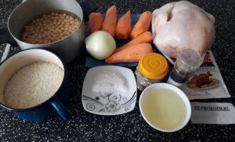 Шаг 1: Подготовьте все компоненты для приготовления плова: курицу, рис, нут, морковь, лук, растительное масло, соль и специи.
