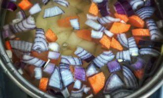 Шаг 2: Почистите и нарежьте картофель, лук и морковь. Залейте водой и варите до готовности овощей.