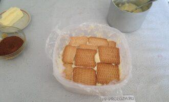 Шаг 4: Форму для торта застелите фольгой или пищевой пленкой. Выкладывайте слоями печенье и крем. Продолжайте формировать торт. Последний слой должен быть из печенья.