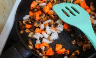 Шаг 4: Добавьте нарезанный лук и морковь. Жарьте еще 5 минут.