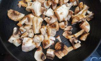 Шаг 3: Нарежьте не сильно мелко шампиньоны, обжаривайте на масле 4 минуты.