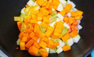 Шаг 5: Тыкву очистите от кожуры, нарежьте, перец тоже нарежьте. И добавьте к овощам в сковороду. Добавьте 100 мл воды. Тушите до готовности овощей 20 минут.