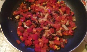 Шаг 4: Нарежьте мелко перец и помидор и добавьте на сковородку. Посолите.