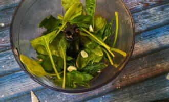 Шаг 3: Положите зелень и чеснок в чашу миксера.