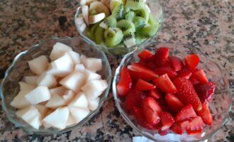 Шаг 2: Хорошо помойте фрукты. Очистите киви, банан, яблоко, грушу и клубнику. Нарежьте небольшими кусочками.