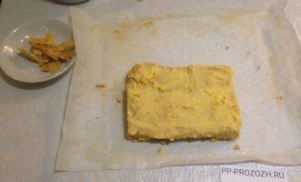 Шаг 8: Соберите торт: обрежьте неровные края коржа по контуру (оставьте обрезки для обсыпки), разрежьте корж на 4 части (прямоугольниками). Каждый кусочек намажьте кремом и сложите один на другой.