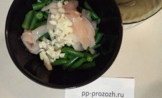 Шаг 4: Туда же добавьте рубленный чеснок, специи и 1 чайную ложку оливкового масла. Все перемешайте.